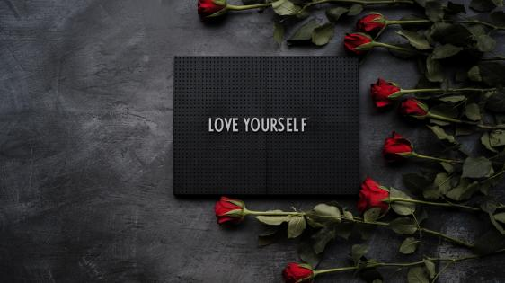 """a slate with the text """"Love Yourself"""" on it with red roses stacked next to the slate"""