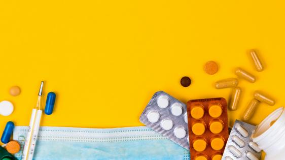 a pile of pills on top of a light blue face mask on a yellow background